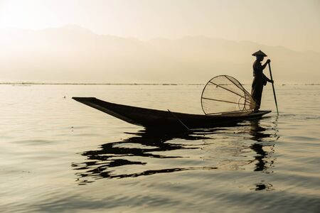 The silhouette of a fisherman on a boat in the morning at Inle Lake is a fresh water lake In the mountainous area of Shan State in Myanmar.
