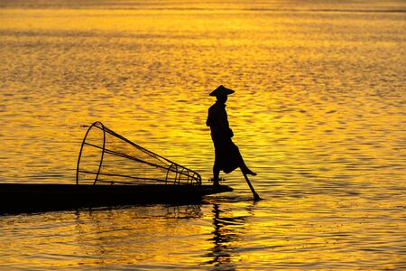 Silhouette of a Burmese man wearing a hat, using paddle legs to catch fish in the evening The water is beautiful orange.