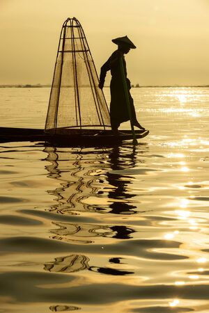 Silhouette Burmese fishermen wearing traditional clothes standing at the back of the boat, preparing morning fishing equipment at Inle Lake, Myanmar