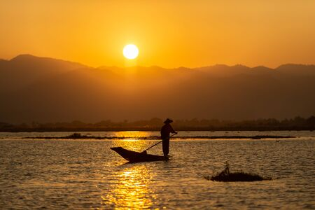 The silhouette of a fisherman on a boat at dusk The sunset is a beautiful orange sky. Inle Lake is a fresh water lake in the mountainous region of Shan State in Myanmar. 写真素材