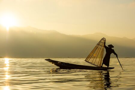 Silhouette Burmese fisherman wearing a hat standing at the back of a boat rowing with legs in the morning, mist faded at Inle Lake, Shan State in Myanmar. 写真素材
