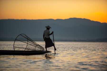 Silhouette of a burmese man wearing a hat Use the rowing legs to catch fish in the evening. The sky is orange beautiful