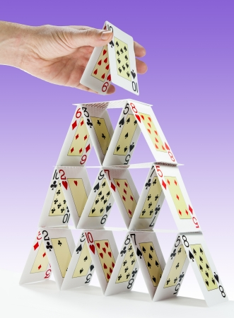 instability: Low-angle view of a man completing a house of cards