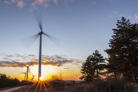 energetically: Windmills rotating energetically in the dawn wind Stock Photo