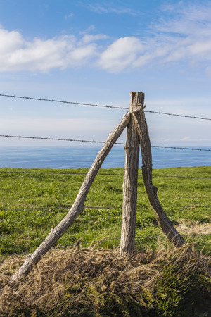 cattle wire: Single fence post propped by two poles Stock Photo