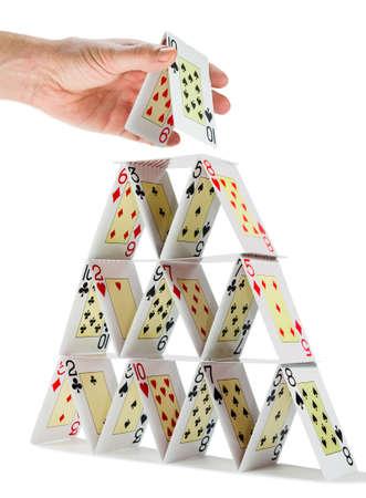 Niedrig-Winkel Ansicht eines Mannes, der Abschluss ein Kartenhaus isoliert auf weiß