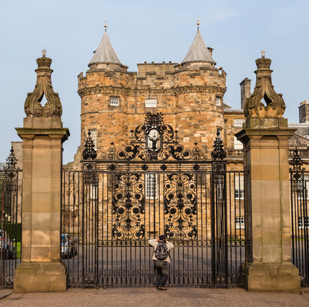 east end: An eager tourist takes pictures from the closed main gates of the Palace of Holyroodhouse, located at the East end of The Royal Mile in Edinburgh, Scotland Editorial