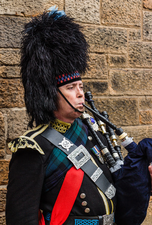 Edinburgh, Scotland - September 14, 2014: Portrait of a military dressed bagpiper playing the bagpipe for the tourists roaming the Royal Mile.