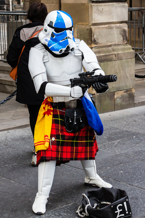 stormtrooper: Edinburgh, Scotland - September 14, 2014: street performer disguised as a kilted Star wars stormtrooper handles a blaster while asking for money. People working in the streets has to use inventiveness to draw spectators around.