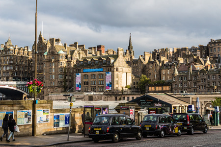 waverley: Edinburgh, Scotland - September 14, 2014: trio of black cab taxis waiting for pick up on Waverley Bridge on a sunny late summer afternoon.