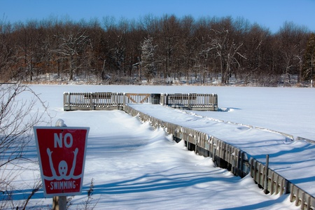 no swimming: A dock in a frozen lake and no swimming sign