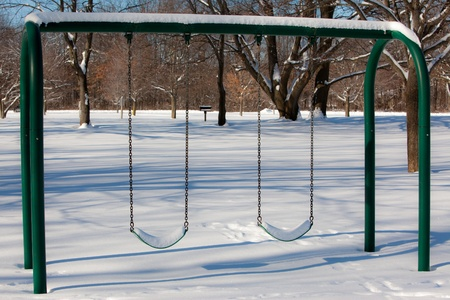 A winter scene of a snow covered pair of swings photo
