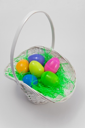 An Easter Basket Containing Colorful Plastic Eggs With Green Grass The Object Is Isolated