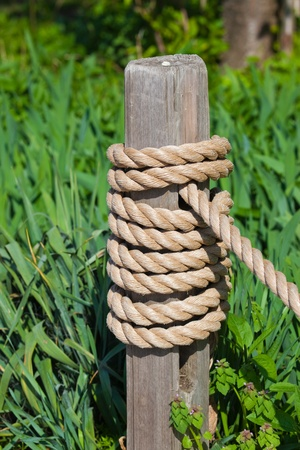 This is a photo of a post with a rope coiled around it  Green grass is in the background