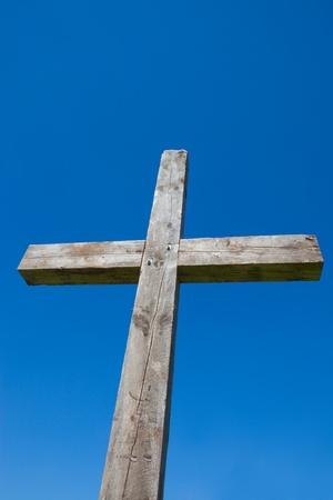 cruz religiosa: Esta es una foto de una cruz de madera tomada mirando hacia arriba en un cielo azul de fondo. Foto de archivo
