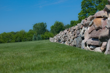 This is a photo of a field stone wall with blue sky and green grass.