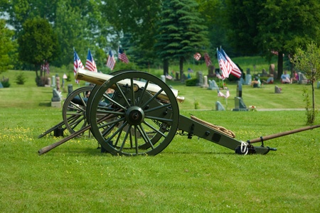 This is a photo of a civil war cannon resting in a grassy field.