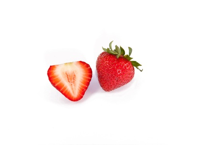 This is a photo of fresh strawberries isolated on a white background. One of the berries is cut in half. Stock fotó