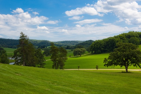 This is a photo of a country landscape with rolling hills and a blue sky with clouds. Stock fotó