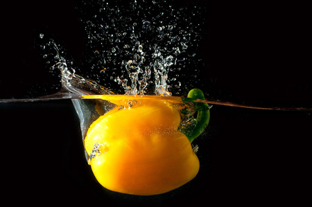 clearly: Yellow pepper falls in the water before black background