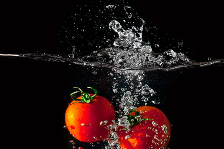 Two tomatoes falling into water before black background