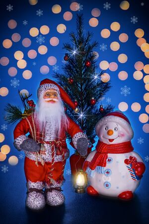 Santa Claus, Snowman and Christmas Tree on a dark blue background with bokeh. Stock fotó
