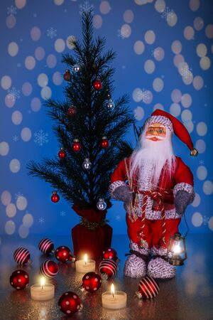 Santa Claus and Christmas Tree on a dark blue background with bokeh. Stock fotó