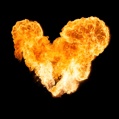 orange inferno: Heart shaped fireball isolated on a black background