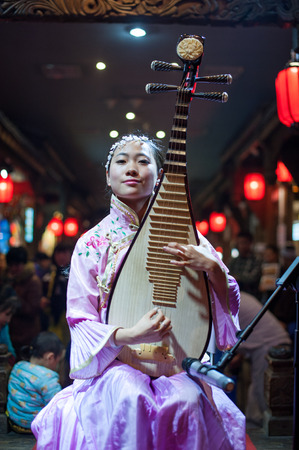 sichuan province: Chengdu, Sichuan Province, China - December 29, 2014: Chinese musician girl playing traditional chinese guitar or piba onstage at Chunxifang Chunxilu. Editorial