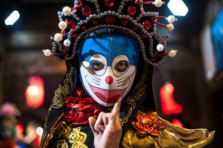 sichuan province: Chengdu, Sichuan Province, China - December 29, 2014: Chinese artist perform traditional face-changing art or bianlian onstage at Chunxifang Chunxilu. Editorial