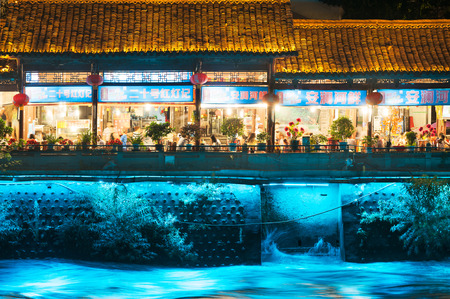 sichuan province: Dujiangyan, Sichuan Province, China - July 25, 2015: People in a restaurant by the river at night. Editorial