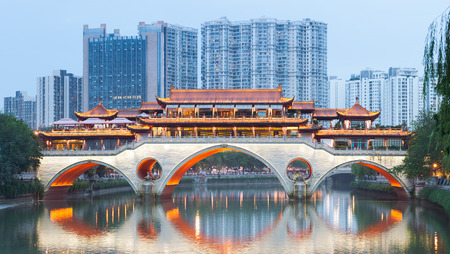 Anshun Bridge against modern buildings at dusk in Chengdu, Sichuan Province, China