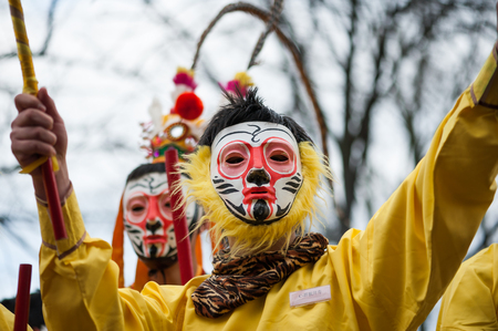 Paris, France - Feb 6, 2011: Chinese performers wearing a monkey mask in traditional costume at the chinese lunar new year parade Éditoriale