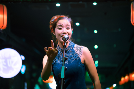 arts culture and entertainment: Chengdu, Sichuan Province, China - September 18, 2015: Chinese female artist sings traditional chinese song for the daily show in Chunxifang Chunxilu covered street.