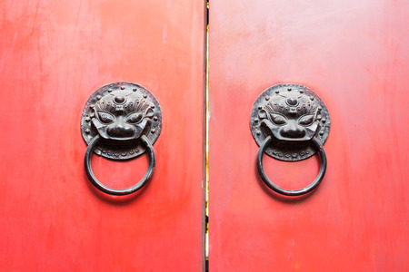 Chinese door knockers on a red closed gate