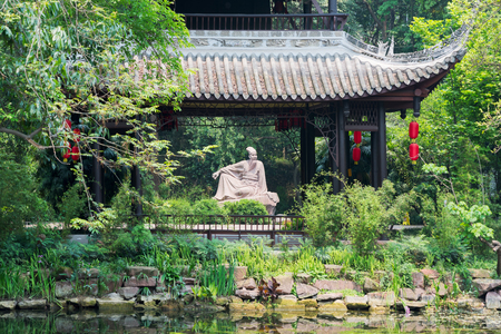 Meishan, Sichuan Province, China - Apr 30, 2017: Su Shi poet sculpture behind a pavilion in Meishan