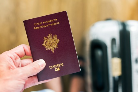 Hand holding a french - european passport with luggage in the background