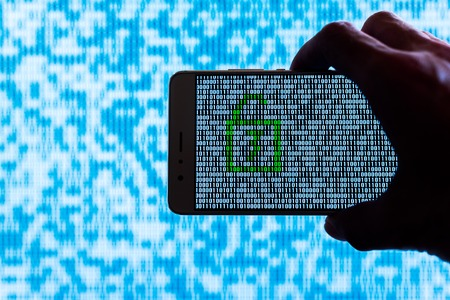 Hand holding a smartphone with a locker unlocked against binary code on screen