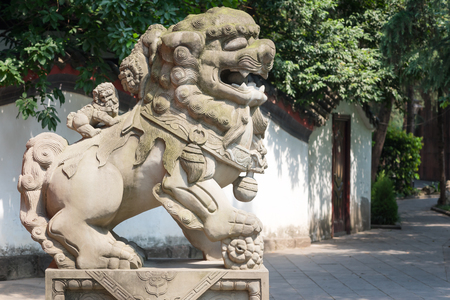 Lion stone statue with two small lions on the back in a park, Chengdu, Sichuan Province, China