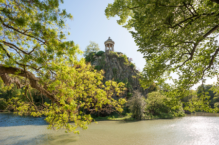 Temple de la Sibylle, inspired by the Temple of Vesta in Tivoli at the top of a rock in the middle of a lake with trees in the foreground - Parc des Buttes Chaumont - Paris Stock Photo