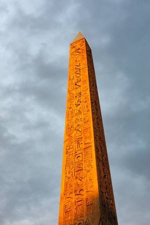 Concorde Obelisk in orange light from sunset against cloudy sky in Paris, France Editorial