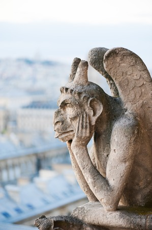 gargouille: Gargoyle on a Paris roof with the city in the background