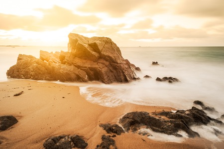 ocean waves: sunset on a beach with rocks Stock Photo