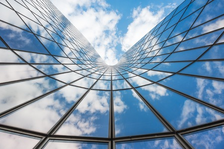 Blue sky and white clouds reflecting in a  glass building