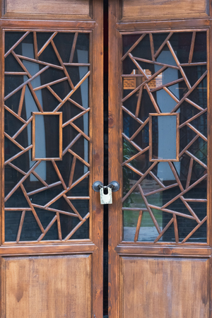 Wooden door locked with decorative glass Stock Photo