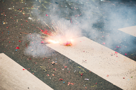Firecracker exploding on the asphalt of a street