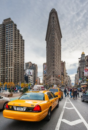 Taxis in a street with the flatiron building in the background 에디토리얼