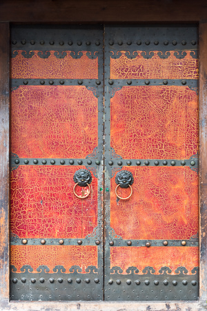 Red cracked paint chinese traditional door with door knockers Stock Photo