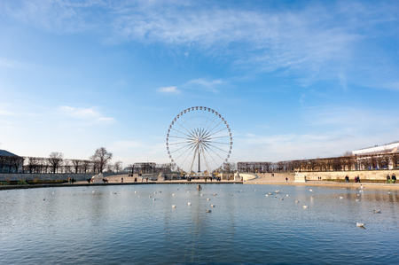 Paris ferris-wheel against blue sky from the Tuileries park with Editorial