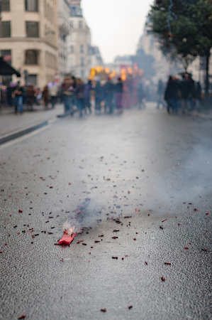 Red firecrackers exploding with smoke on the asphalt with peolple in the background for the chinese new year 写真素材